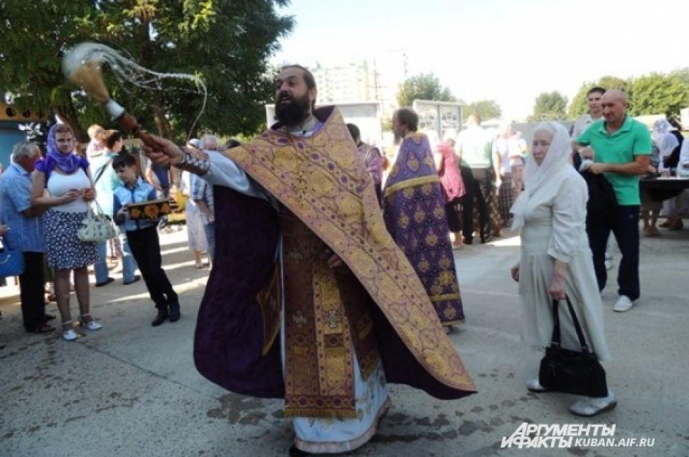 Отец Василий окропляет прихожан святой водой.
