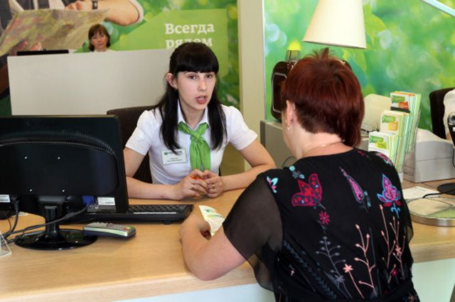 Сотрудница отдела кредитования общается с клиентом банка.