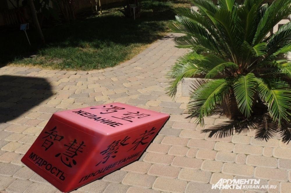 Этот объемный куб с талисманами-иероглифами на самом деле – плоский лист, лежащий на асфальте.