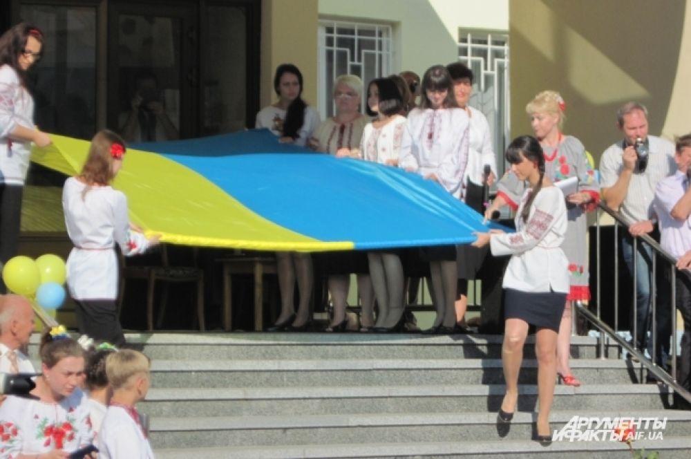 Старшеклассники выносят государственный флаг Украины