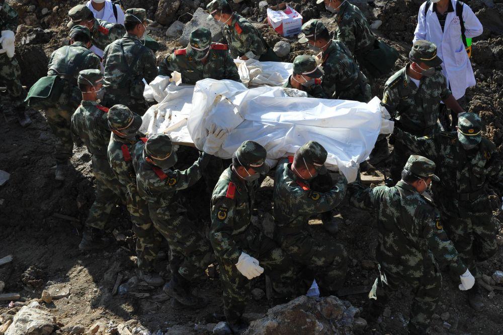 Спасатели выносят тело погибшего.