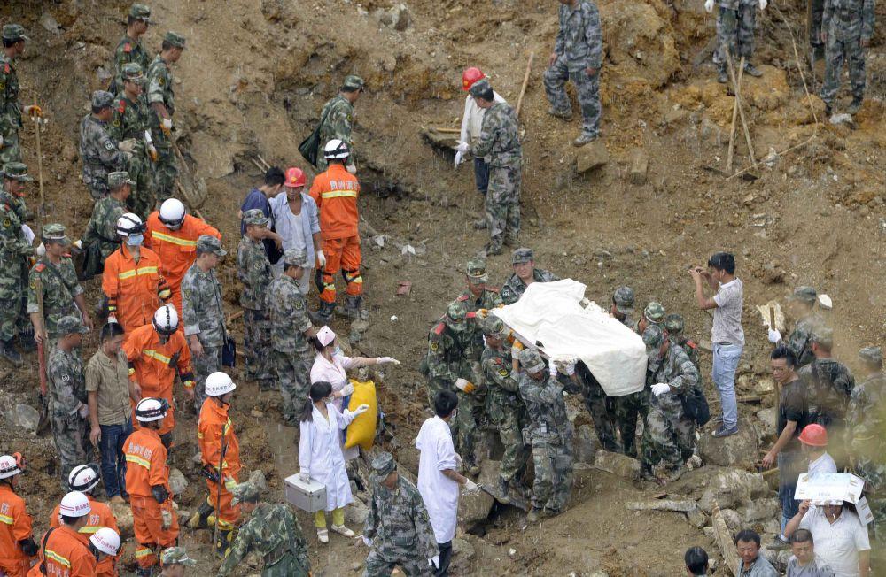 Спасатели несут тело жертвы.
