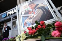 Цветы в память о погибшем на Украине фотокорреспонденте Андрее Стенине у здания агентства МИА «Россия сегодня».