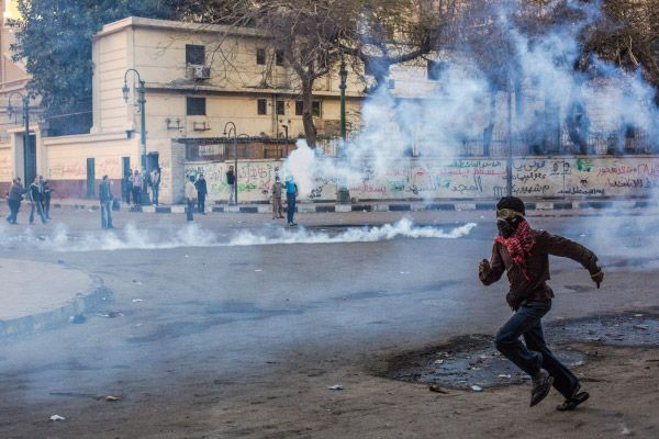 Участник акций протеста во время столкновений с полицией возле площади Тахрир в Каире.
