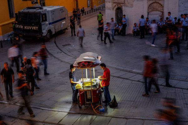 Продавец вареной кукурузы и полицейские на улице Истикляль возле площади Таксим.