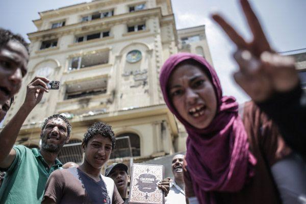 Протестующие у разгромленного здания штаб-квартиры политического движения «Братья-мусульмане» в Каире.