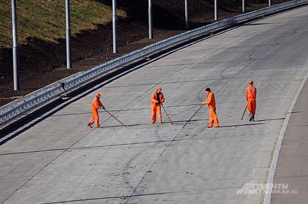 Пока монтажники-высотники доводят мост до готового состояния, дорожные рабочие чистят бетон, на который скоро положат асфальт.
