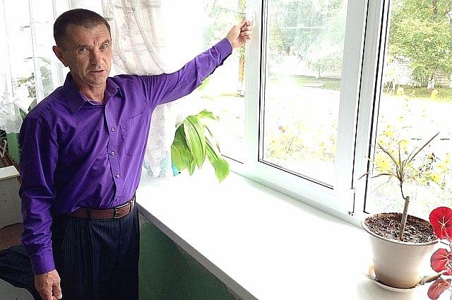 Директор школы с радостью демонстрирует новые окна.