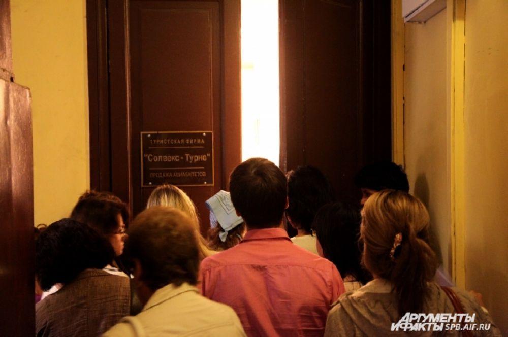 Двери турфирмы пропускают маленькие группы людей, желающих забрать документы.