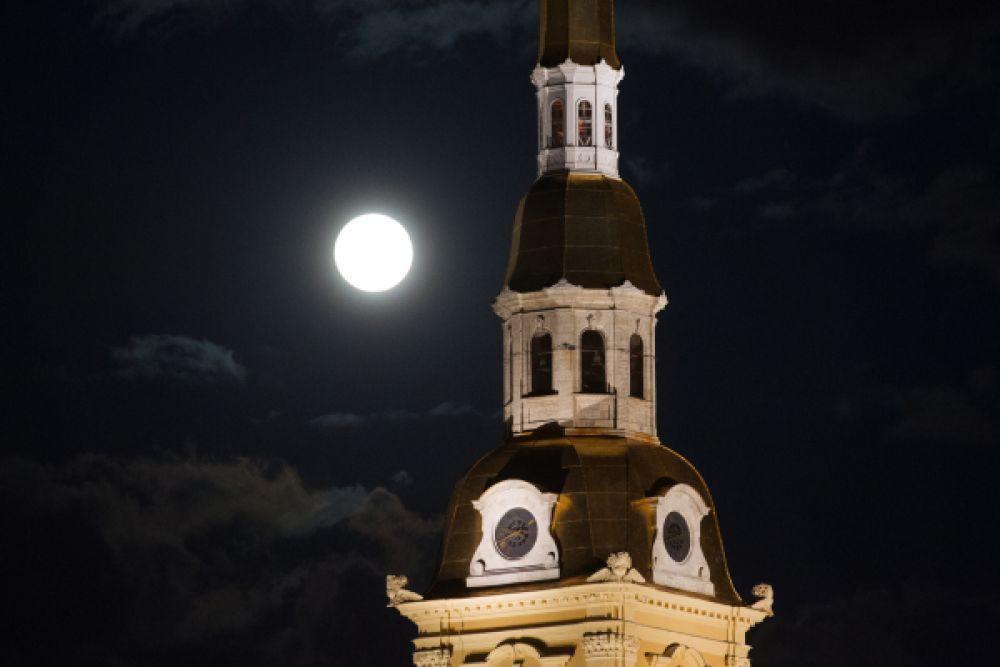Взгляд на суперлуние со стороны  Петропавловского собора в Санкт-Петербурге.