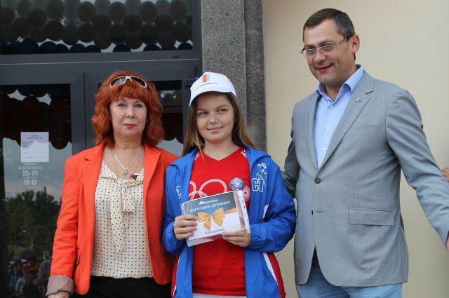 В. Иванов и Н. Коковина вручают подарочные сертификаты участникам велопробега в День российского флага.