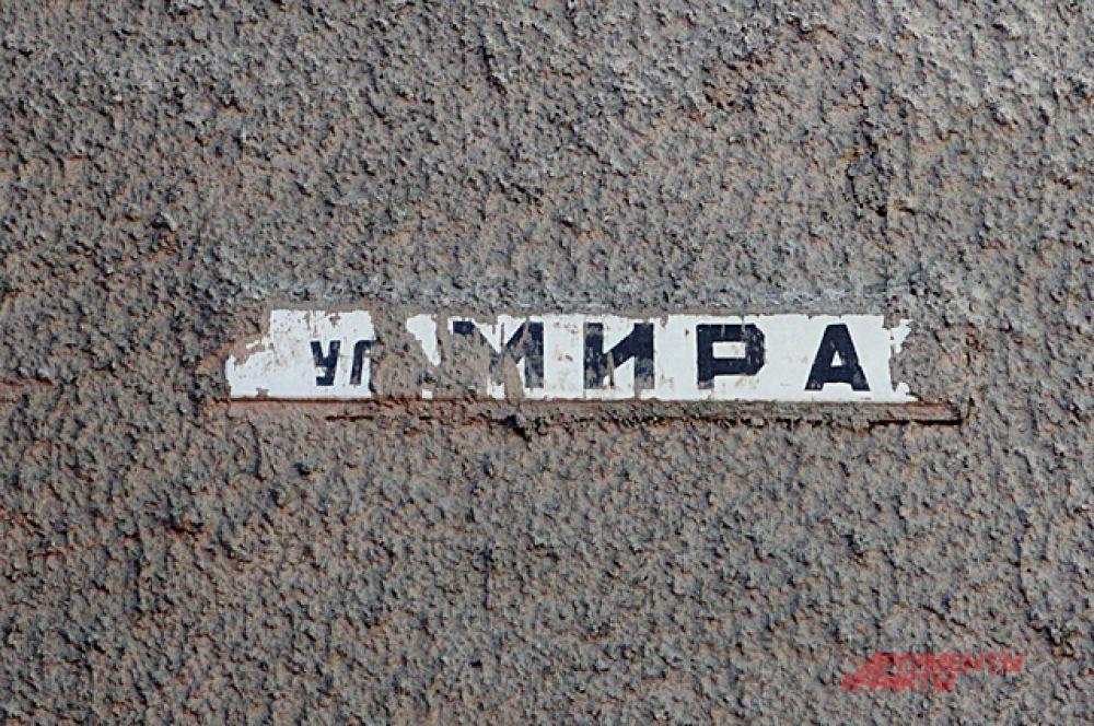 Табличка под слоем цемента намекает, что её прикрутили ещё до нанесения облицовки здания.
