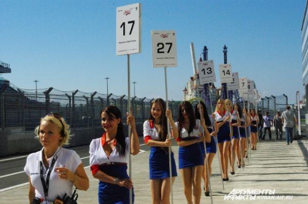В это время к старту направляются красотки с табличками в руках. По этим номерам будут выстраивать на старте машины пилотов.