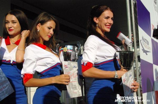 Девушки-модели готовятся награждать победителей гонки.