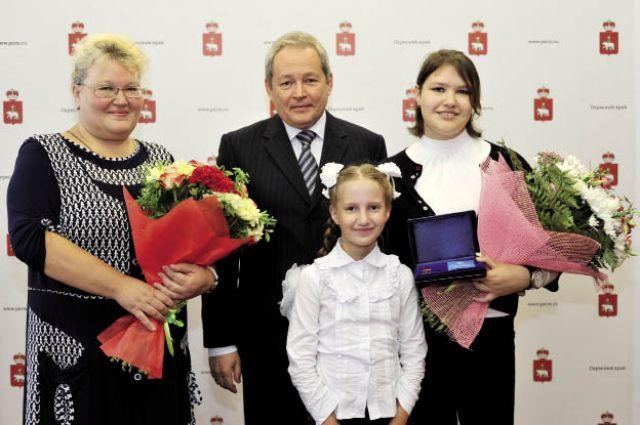 На вручение памятного знака Аня пришла вместе с мамой и сестрой.