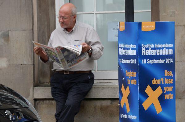 Мужчина у агитационного щита. Надпись на щите: «Используй, а не теряй свой голос».