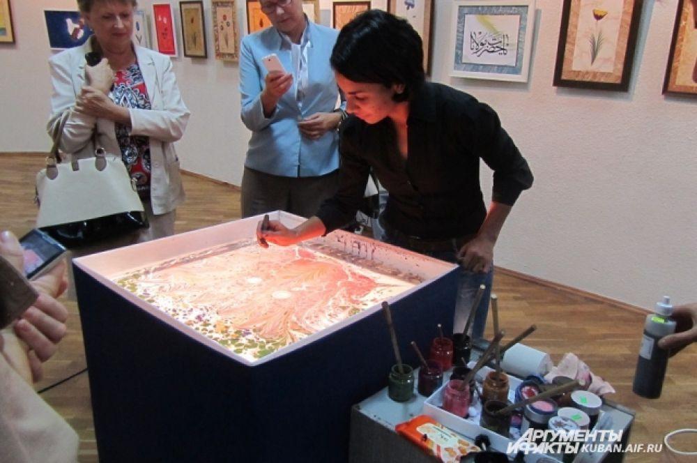 Краснодарская ученица Гарипа Ай Рената Нисимова демонстрирует посетителям выставки, как создается живопись на воде.