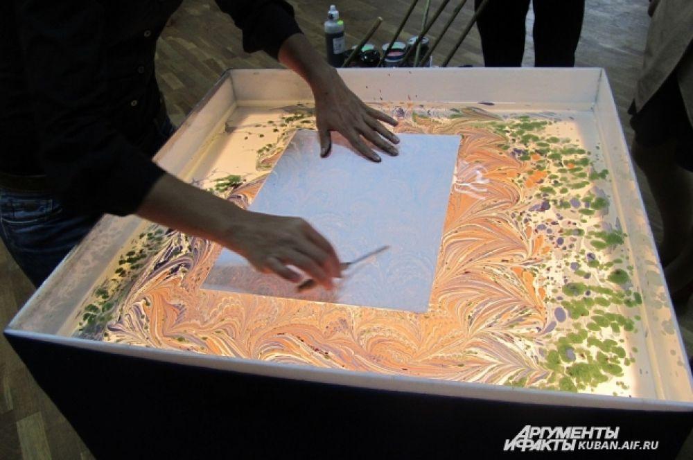 Когда картина готова, художник кладет на воду лист обычной бумаги, краски впитываются, и получается своеобразный оттиск.