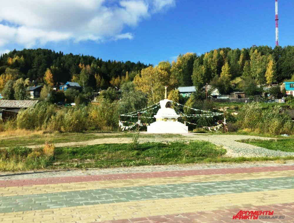 Буддийская ступа по улице Набережной от порывов ветра размахивает цветными ленточками.