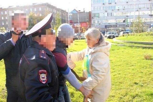«Православный активист» разрывает антивоенный плакат, который держала женщина почтенных лет.