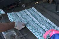 Во время  досмотра у них нашли крупную сумму денег, а также несколько купюр номиналом 5 тысяч рублей с признаками подделки.