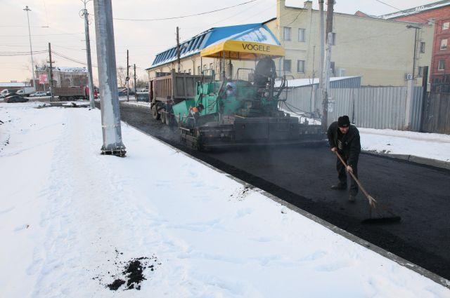 Выпавший снег не мешает дорожникам Челябинска укладывать асфальт.