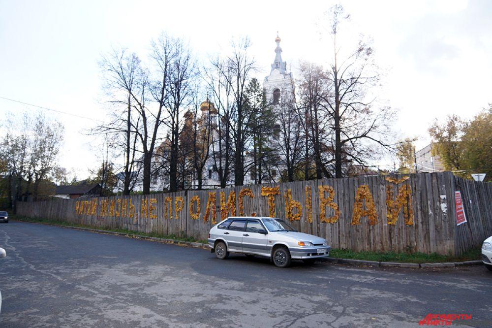 Арт-объект переставляет собой надпись «Читай жизнь, не пролистывай», созданную с помощью осенней листвы, приделанной к доскам.