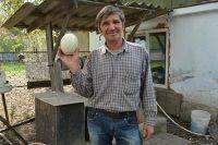 Валерий Королёв демонстрирует страусиное яйцо весом в два килограмма.