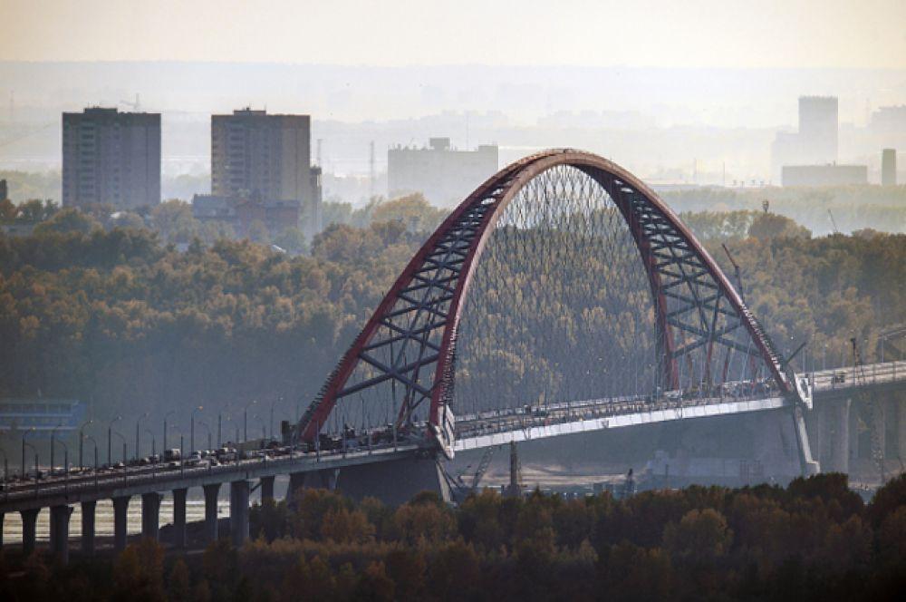 Возведение моста в Новосибирске началось в феврале 2010 года. На его строительство ушло почти 17,1 млрд рублей. Протяженность полотна составляет около 5,5 км, а его самый впечатляющий пролёт поддерживают 160 вант, закрепленных на 380-метровую арку. Пропускная способность моста – 60 тысяч автомобилей в сутки. В ходе презентации Владимир Путин напомнили, что 10-рублевая купюра, на которой изображен Красноярский мост, выходит из обихода, и предложили для укрепления финансовой системы выпустить купюру, на которой был бы изображен Новосибирский мост.