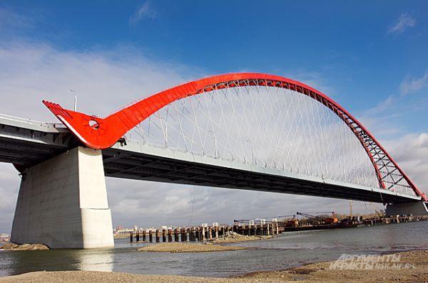 Арка моста выполнена в виде стилизованного лука - стрелкового оружия. Почти такой же лук - лежит в основе новосибирского герба и восходит своей историей к седой сибирской древности.