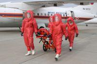 Сотрудники МЧС России везут медицинский модуль вовремя презентации самолёта, предназначенного для перевозки инфицированных лихорадкой Эбола.