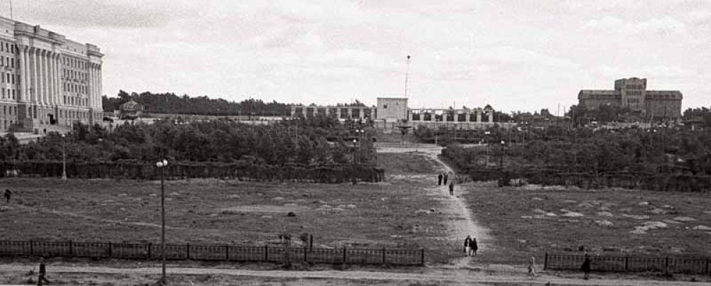 Место нынешней площади Революции, конец 1940-х — начало 1950-х годов. Площадь представляет собой заросший кустарником кусок земли. Вдалеке можно разглядеть фонтан, который в этом году стал уже «поющим». По обе стороны от него — березовый лес. Справа — элеватор, который недавно признали одним из страшнейших зданий России. Изначально площадь называлась Южной, в площадь Революции она была переименована в 1920 году. Через год на месте Одигитриевского женского монастыря возвели гостиницу «Южный Урал». А памятник Владимиру Ленину установили только в 1959 году.