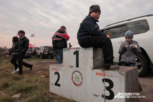 Юные болельщики жду начала гонок на пока пустующем пьедистале