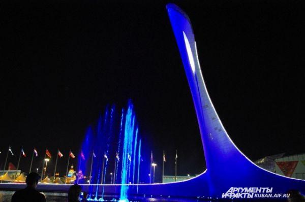 Олимпийский факел при ночной подсветке.