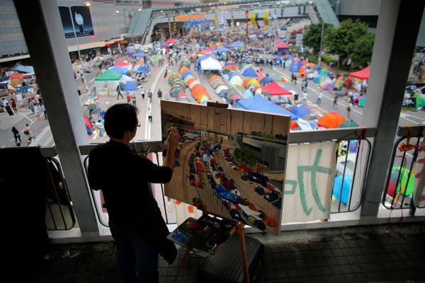 Художник рисует картину протеста перед зданием штаб-квартиры правительства, где протестующие продолжают блокировать прилегающие районы в Гонконге.