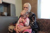 Татьяна Лоренс держит на коленях двухлетнюю Амалию.