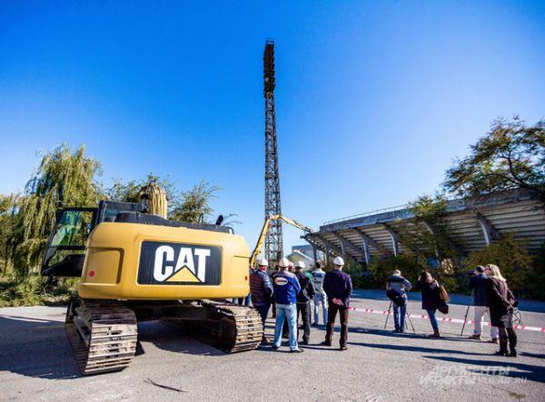 Экскаватор-погрузчик «CAT» дожидается своей очереди. Ему предстоит переместить строительный мусор в «КамАЗ», который вывезет его за пределы площадки.