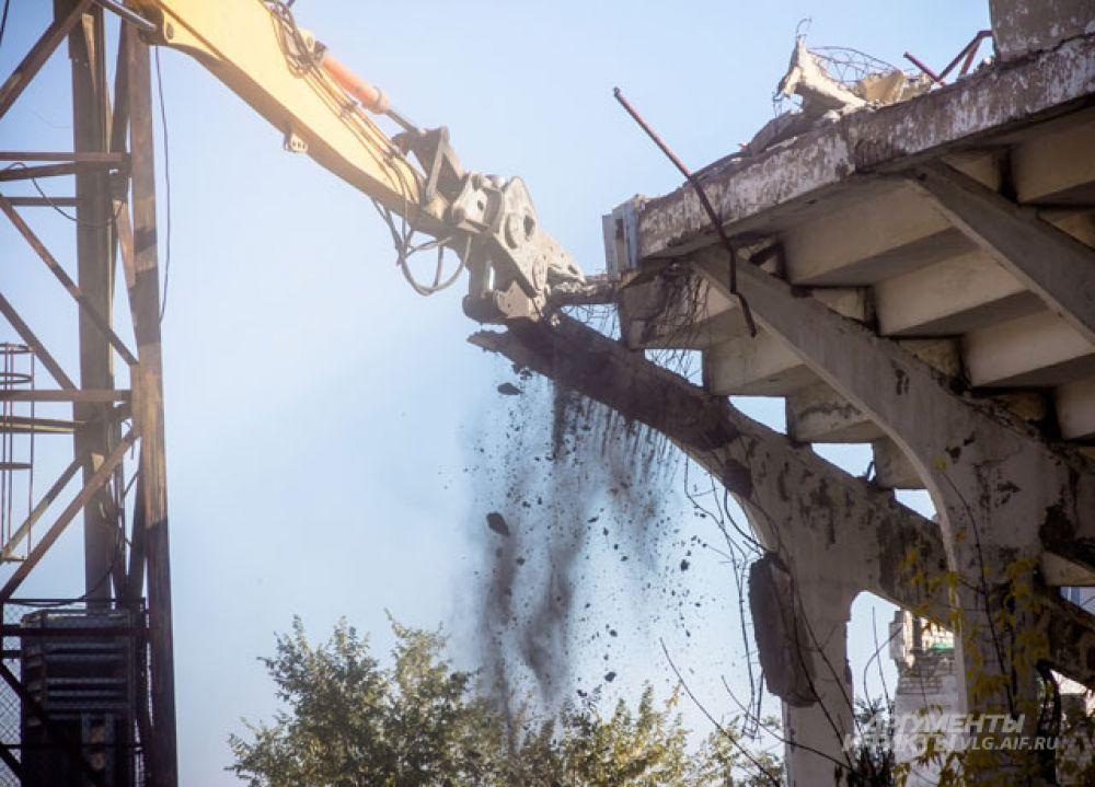 Специальная машина по частям «откусывает» бетонную конструкцию.