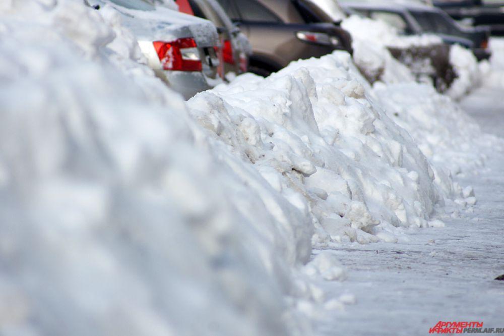 Большие снежные сугробы расположились почти на всех тротуарах Перми.
