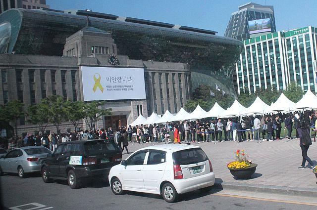 На мэрии Сеула установлен плакат с жёлтой ленточкой - символом памяти и скорби о погибших детях.