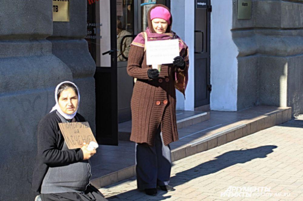Трудно сказать, что может заставить беременную женщину стоять на коленях на асфальте в морозный день.