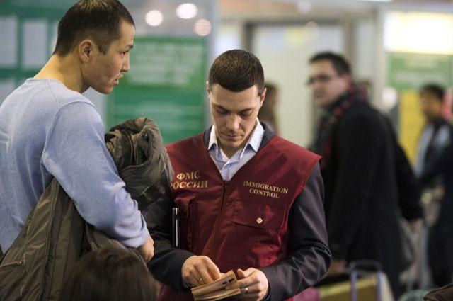 Сотрудник ФМС России проверяет документы у иностранного гражданина.
