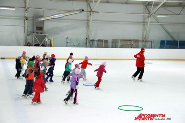 На льду рассыпаны обручи - это препятствия, которые дети должны преодолевать.