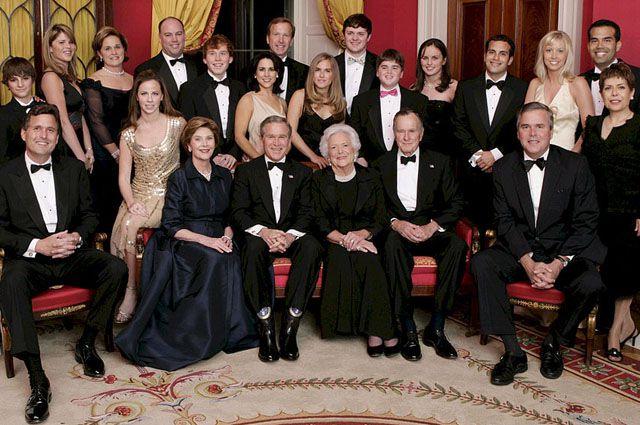 Джордж Буш-младший, Лора Буш, бывшая первая леди США Барбара Буш, и бывший президент Джордж Буш-старший сидят в окружении семьи в Красном зале, 6 января 2005 года.