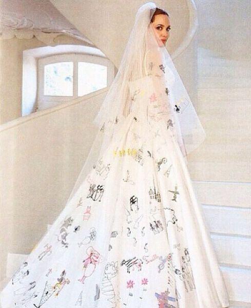 Анджелина Джоли. Дизайн платья невесты разработали дети пары - Шайло, Мэддокс, Пакс, Захара, Вивьен и Нокс. Портной из ателье Versace Луиджи Масси использовал десятки детских рисунков и разместил их на подоле платья и свадебной фате