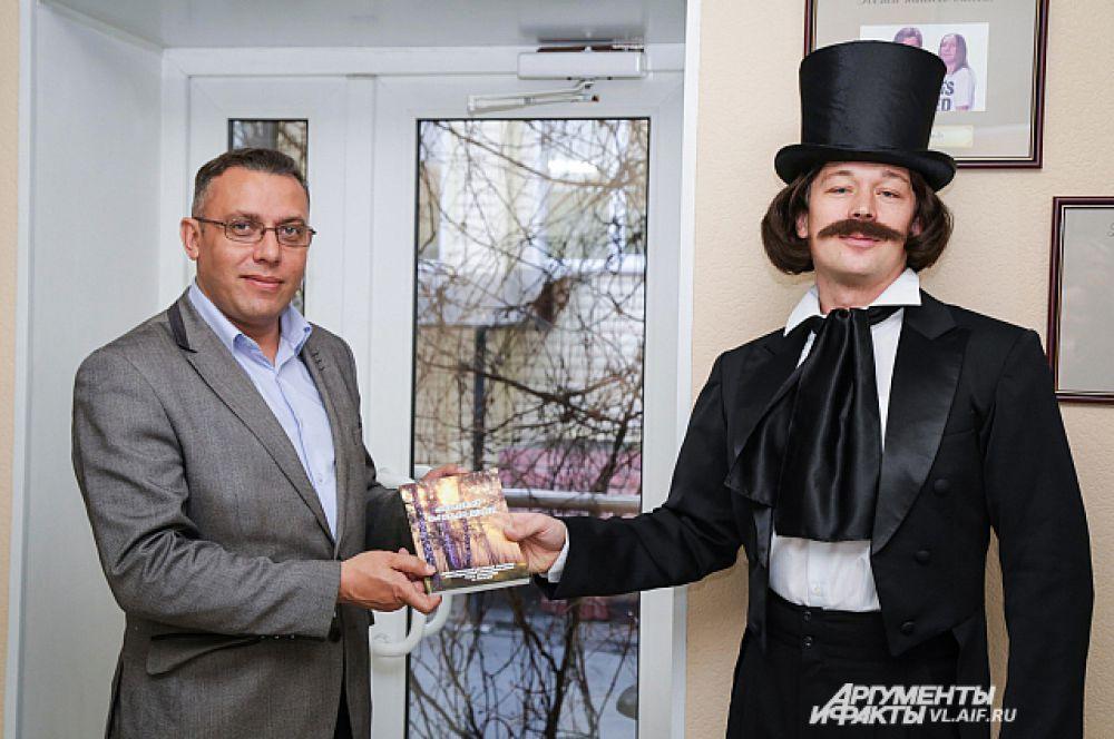 Гоголь вручает победителю экземпляр книги.