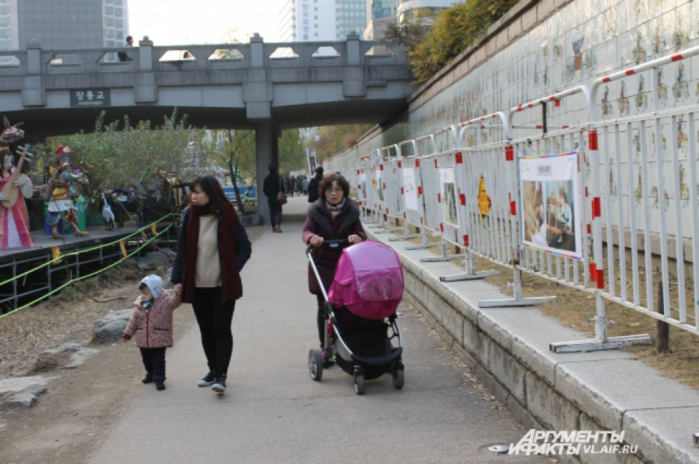 Набережная в центре Сеула. Мамы прогуливают детей вдоль городской реки.