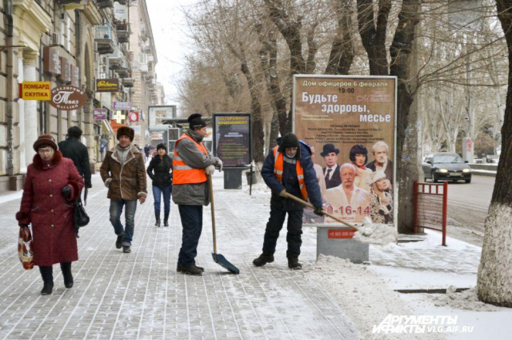 Рабочие очищают тротуары.