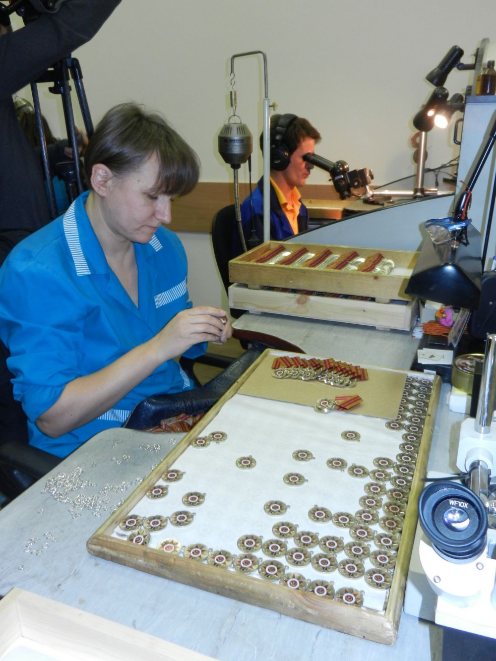 На участке сборки продукцию тщательно просматривают, в том числе в микроскоп. Не должно быть даже малейшего изъяна. Сейчас рабочие выполняют ответственный заказ. На Монетном дворе делаю медали в честь 70-летия Победы.