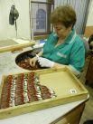 Зоя Честнейшина, которая около 30 лет проработала на предприятии, сейчас трудится на сборке наград. За смену ей надо сделать 2 тысячи медалей. Однако благодаря огромному опыту и сноровке план она перевыполняет регулярно.